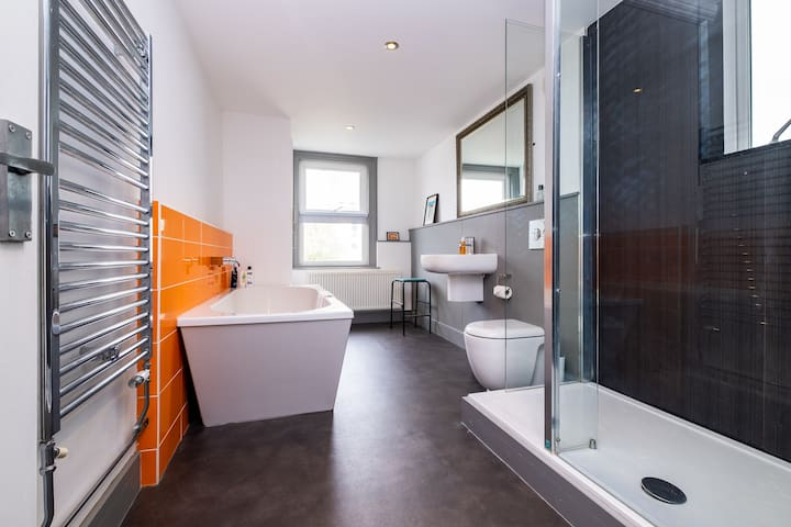 Large luxury family bathroom with large bath and shower. Fluffy white towels are provided for all guests.