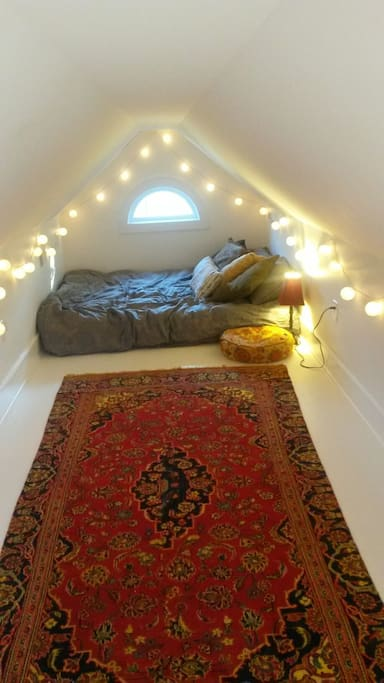 Cozy queen mattress in boho loft area.