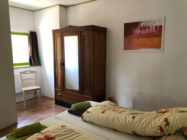 1e slaapkamer met twee een persoons boxspring bedden, kast, inclusief bad- bed en keukenlinnen, en de bedden zijn opgemaakt.