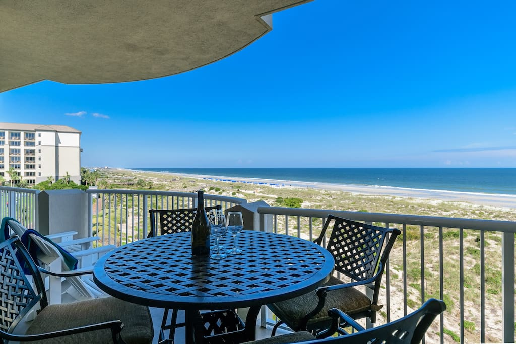 Dining table and chairs are bar height for unobstructed views above the railing.