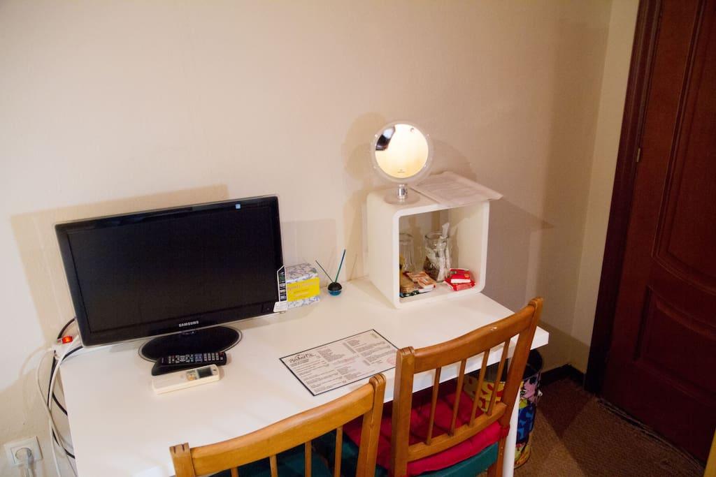 Mesa de escritorio con monitor de TV, regleta para otros aparatos eléctricos, espejo de aumento ideal maquillaje y sillas para su comodidad.
