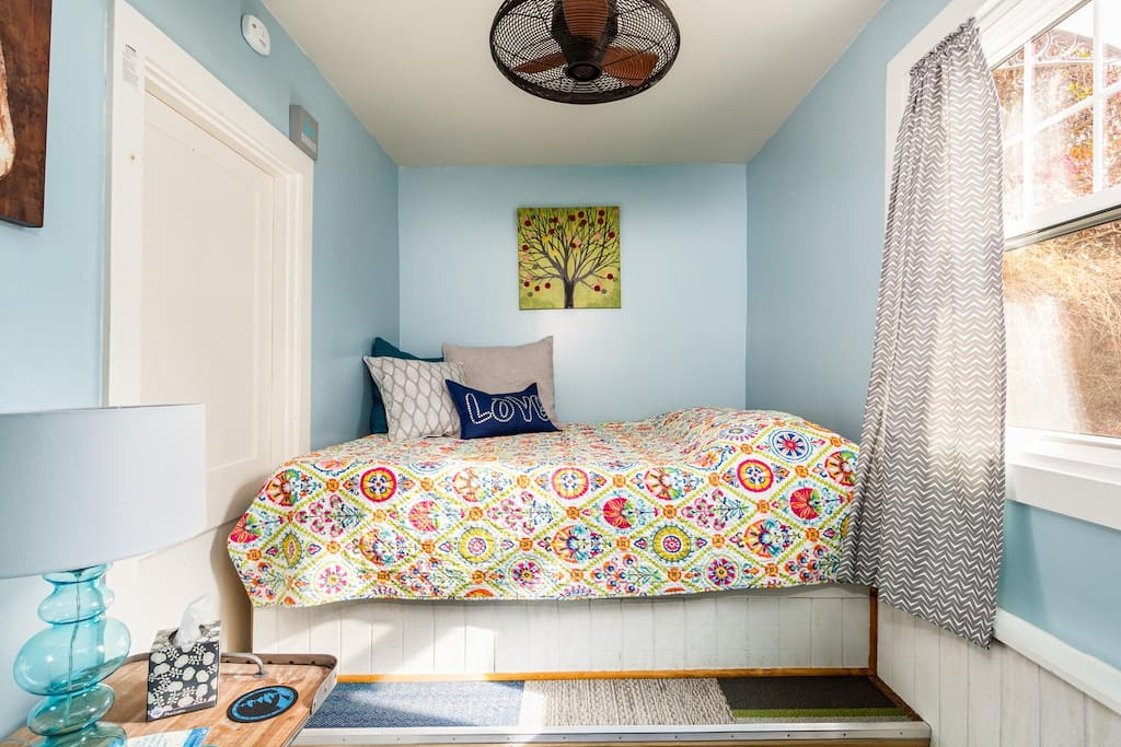 Quiet bedroom with platform bed and ceiling fan.