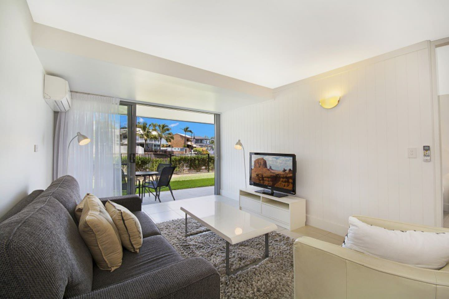 Lounge with glass sliding doors which open up to manicured lawn area with Noosa River and sunset view