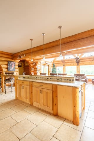 Open Island with seating for 6and next to it is a rounbd glass table perfect for adults hanging out while dinner is prepared or for kids to keep an eye on, your entire party can sit for dinner in this custom log home