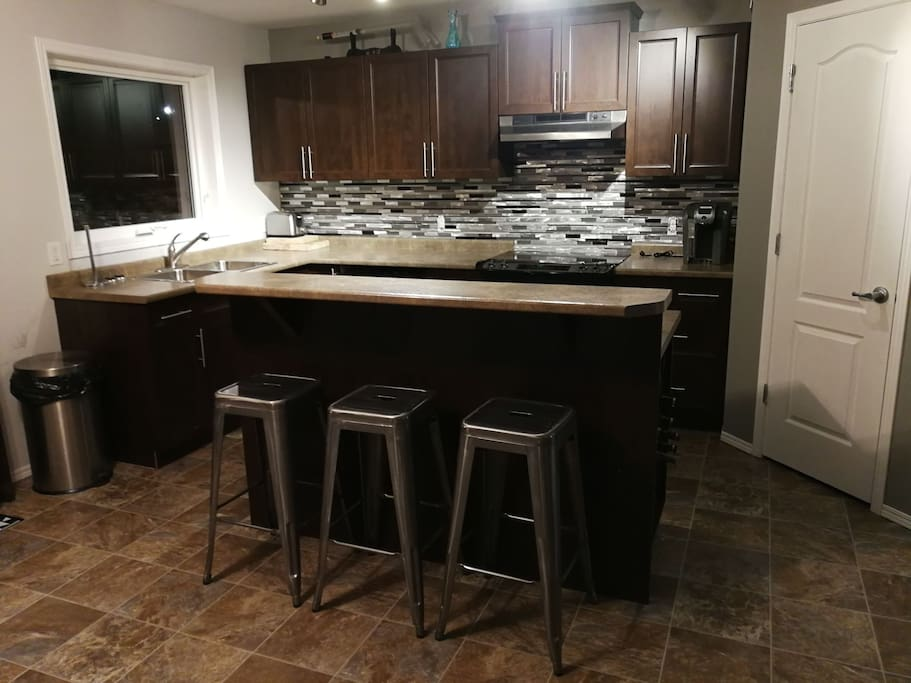 large eat-in kitchen with Island bar stools bar fridge newer cooking appliances.