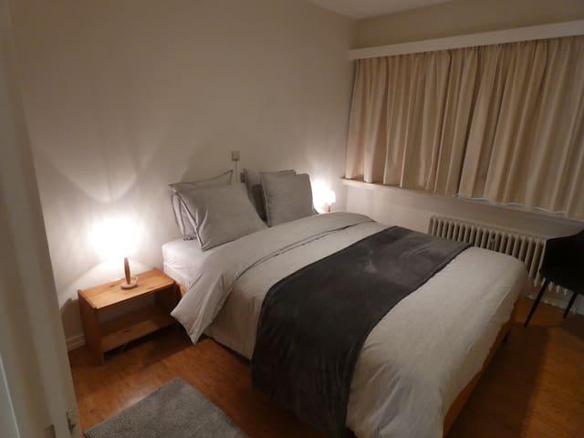 Slaapkamer met dubbel bed en inbouw kleerkast. Achteraan smal terras.