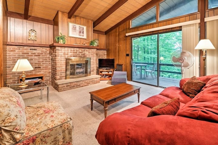The impressive living room features vaulted ceilings and a brick fireplace.