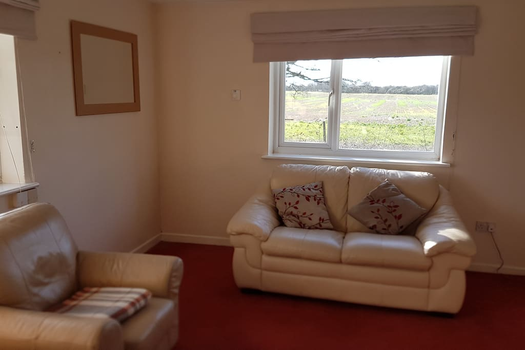 Lounge with double aspect windows over fields