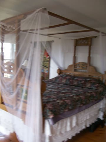 The British Raj room. Antique canopy bed with mosquito netting.