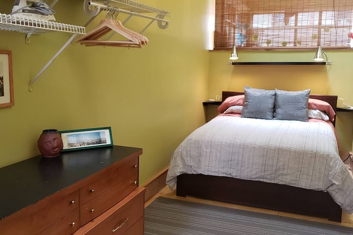 The bedroom features a full-size bed, dresser, clothes rack, and plenty of extra blankets.
