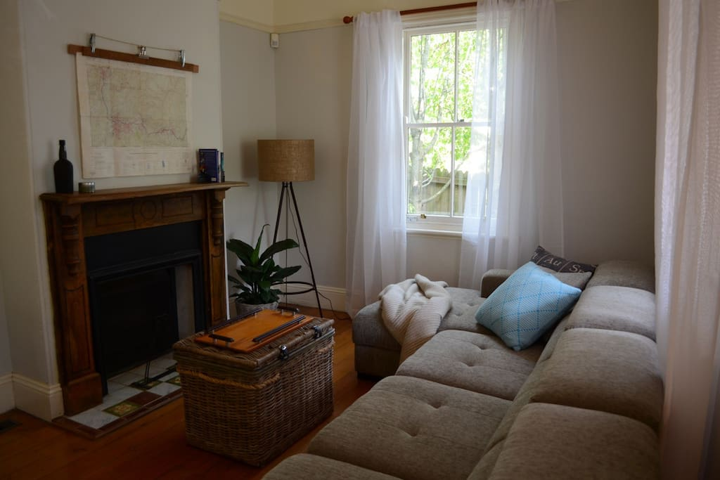 Front living with open fireplace with extra long couch to relax in comfort