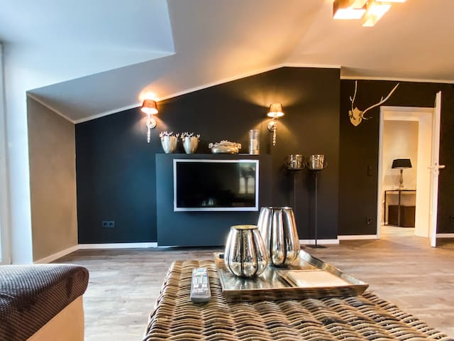 """Die Fernsehwand - In Verbindung mit den übrigen Wänden in Rohputz-Optik beruhigt der Blick auf die Schwarze Wand und lenkt gleichzeitig Ihren Fokus auf den 42"""" LED TV. Die silbernen Dekorationselemente harmonieren dabei mit dem TV-Gehäuse."""