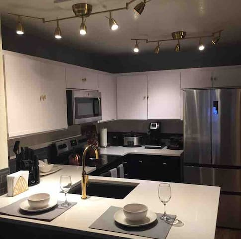 The updated kitchen features bright white quartz countertops, breakfast bar seating for two, and new stainless steel appliances.