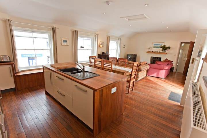 Large open plan kitchen dining and sitting room with beautiful original mahogany flooring.