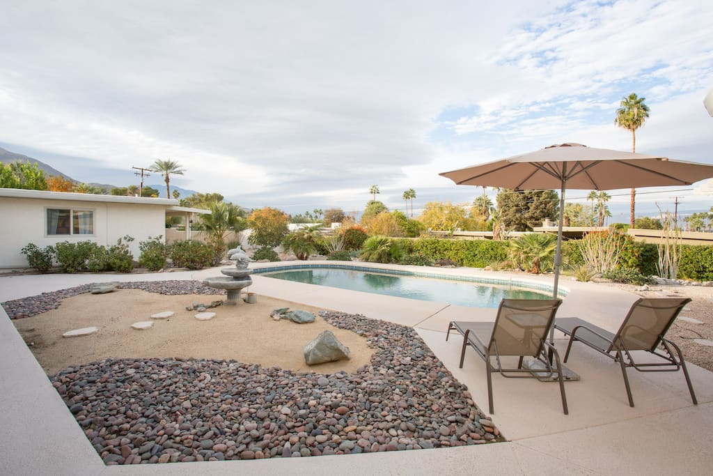 The huge pool with patio furniture