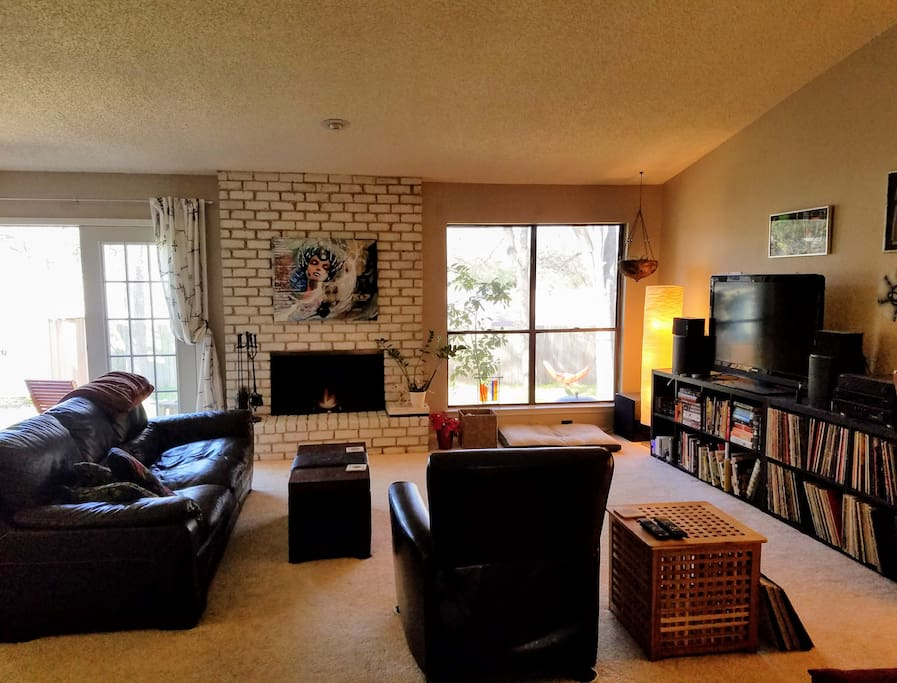 Large living room, opening to the dinning area and to a small patio and green backyard.