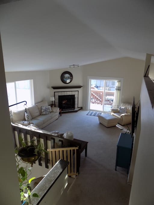 Upstairs living room with fireplace and access to upper deck, stairs to fenced backyard