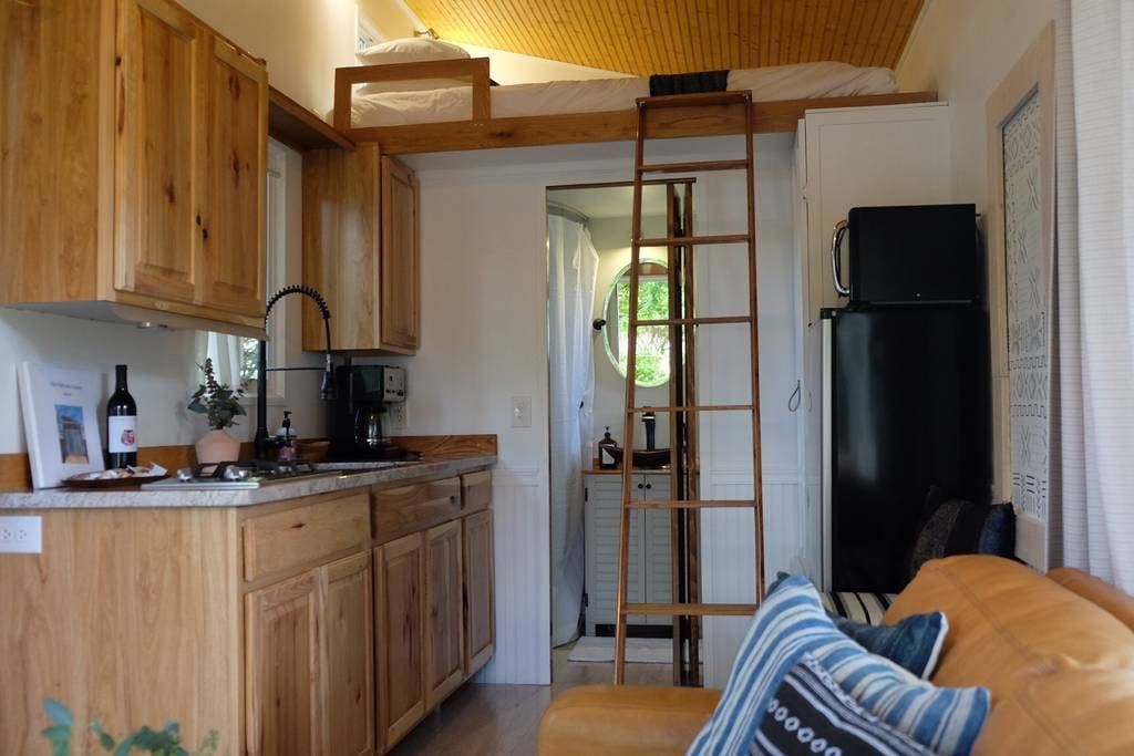 200 sq. ft. of tiny living with kitchen, dining table, bathroom, bed, full size couch and porch!