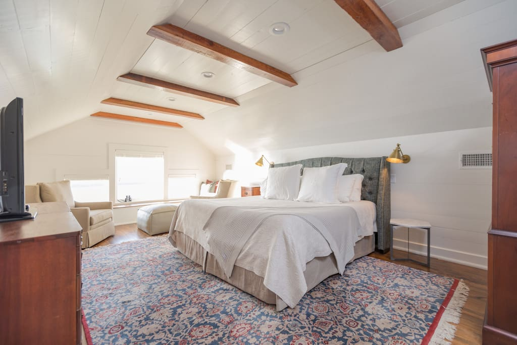"""The Observatory Suite's bedroom features a comfortable king-sized bed -- antique furnishings, and a """"Netflix Monitor"""" (TV with Roku)."""