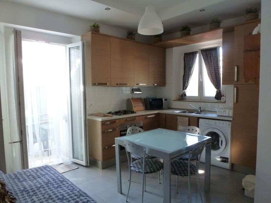 Angolo cucina con accesso a cortile esterno e divano letto
