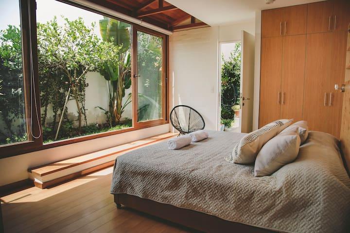 Habitación principal muy iluminada, cama king, baño completo incorporado con jardín y terraza.