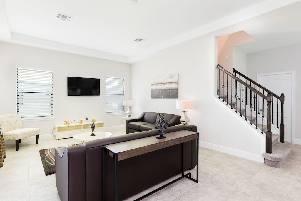 The living area is bright and modern, featuring comfy sofas and a TV.
