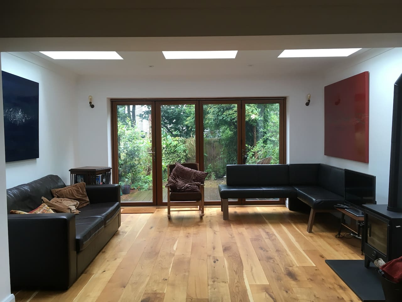 Light filled living room with woodburning stove and tv, opens on to wooden deck and garden.