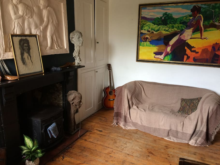 Comfortable sitting room where there are books, a television or guitars for guests to enjoy