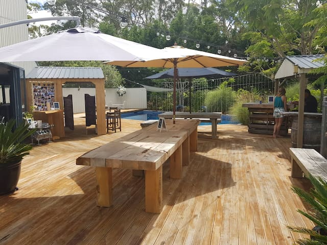 New large tables around the pool, BBQ, pizza oven entertainment area.
