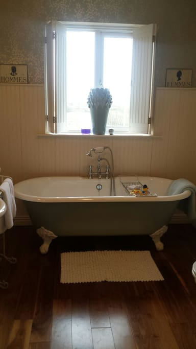 Rolltop old style bath tub in the bathroom right next door to your bedroom