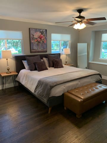 """Master suite with king-sized bed and 55"""" HDTV."""