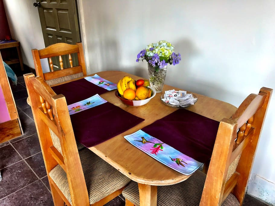 Dinning area with coffee, creamer and sugar, fresh cut organic flowers and organic fruits.