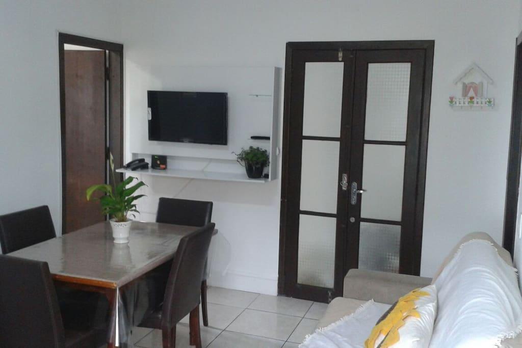 Sala conjugada com cozinha porta esquerda entra quarto com sacada.porta vidro e a principal de entrada.  Smart TV .mesa  . sofá .