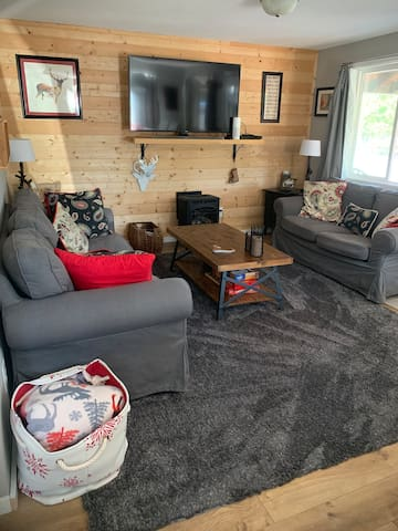 The living room is open to the dining room and kitchen. Features a cozy gas stove, and comfy couches to watch a movie or play one of the many games.  Photo May 2019