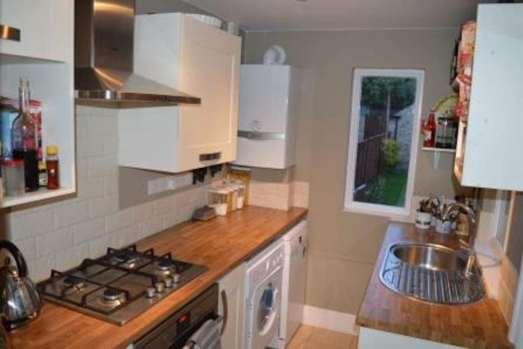 Cute kitchen with door and windows onto the garden. Washer/drier and dishwasher