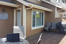 Another view of the spacious deck,   with master bedroom entrance, extra seating, & a family style grill for your bbq'ing delight.