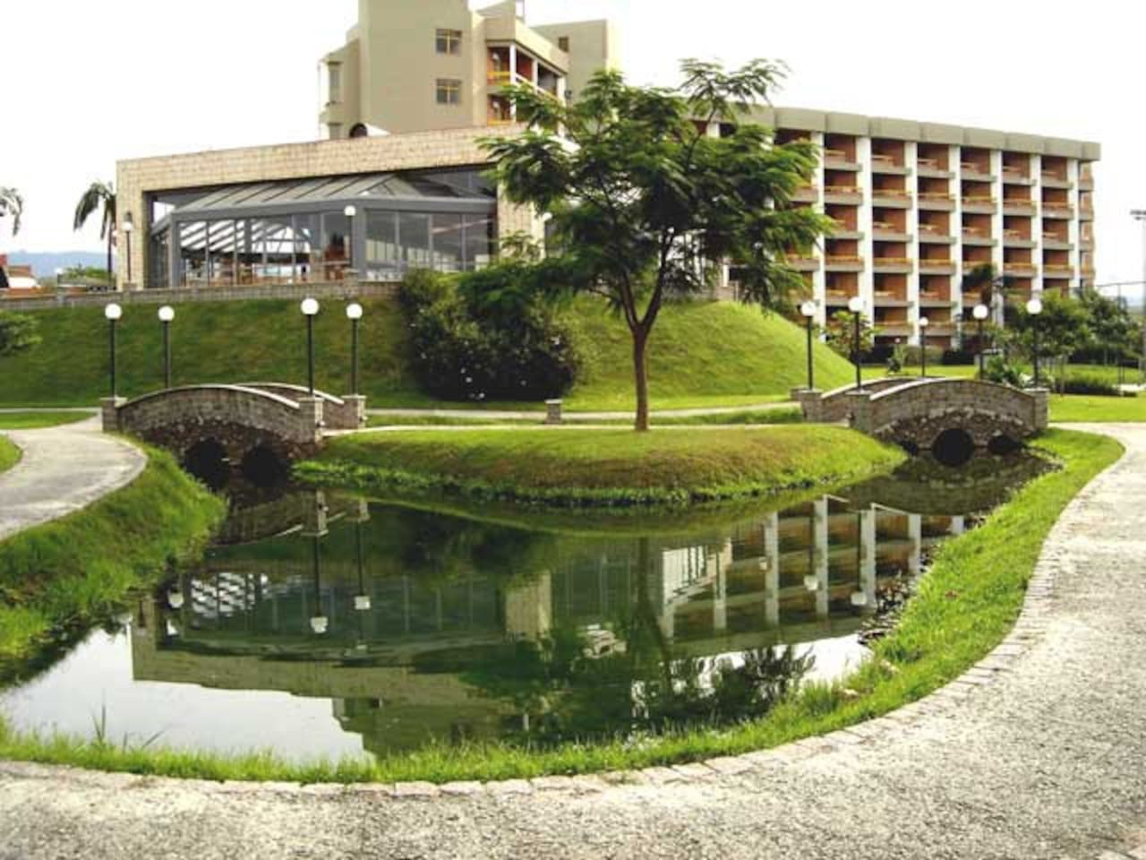 O Jardim, a piscina térmica e o prédio ao fundo.