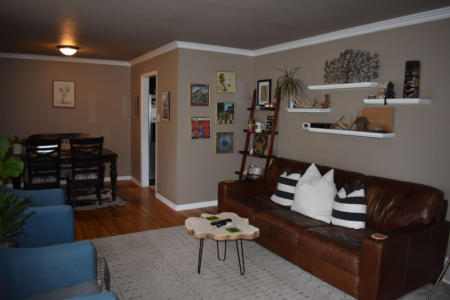 The upstairs dining and living rooms, with functional dining space, cozy couch seating and a TV.