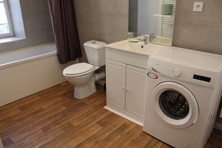 Salle de bain avec baignoire, WC et machine à laver.