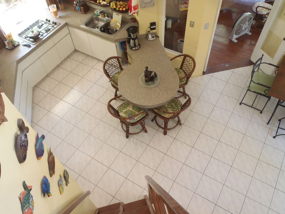 View from upstairs bedroom of fully-equipped kitchen and social area