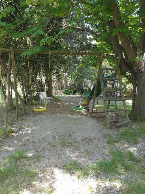 Grand jardin avec toboggan et balançoire accessible aux vacanciers.