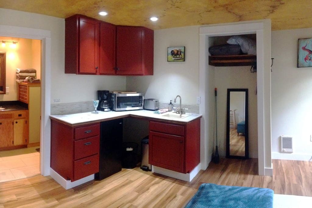 Kitchenette with sink, toaster, microwave, coffee maker, mini fridge, and cooktop. Cupboards and drawers fully stocked with dishes, utensils, coffee/tea, spices, and other essentials. Closet has extra pillows and blankets.