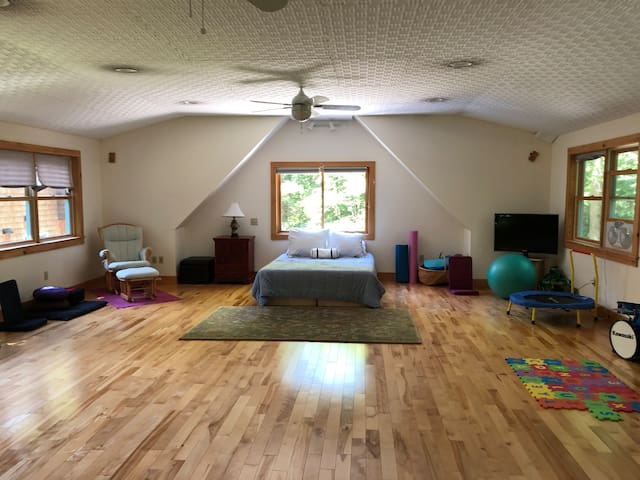 Upstairs studio is completely open, has 360 degrees of windows with views of the treetops, extra queen bed with memory foam mattress, exercise equipment, yoga mats/blocks, meditation cushions, tv for use with DVD player, kids balls/toys/instruments.
