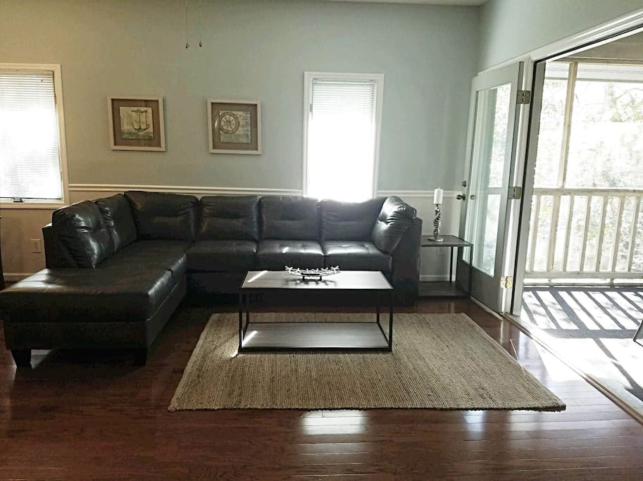 "Living Room; Leather Sectional, 50"" LED Smart TV, French Doors open to screened-in patio."