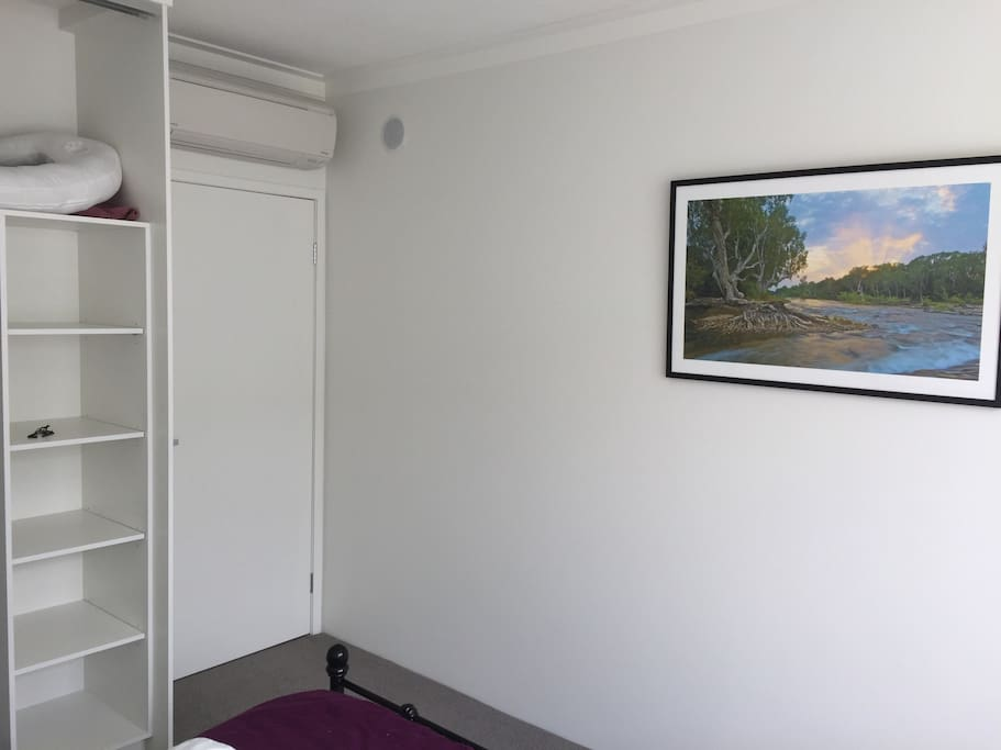 AC unit, beautiful picture of nature and shelves to separate your clothes