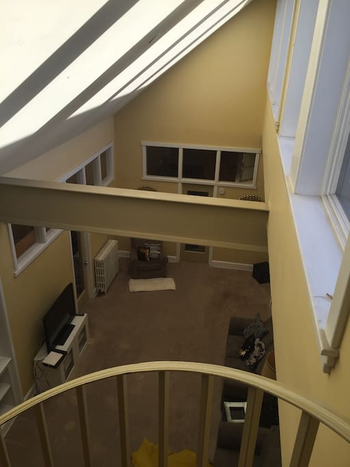 View of living room from the top of spiral steps. Steps lead to the outdoor space