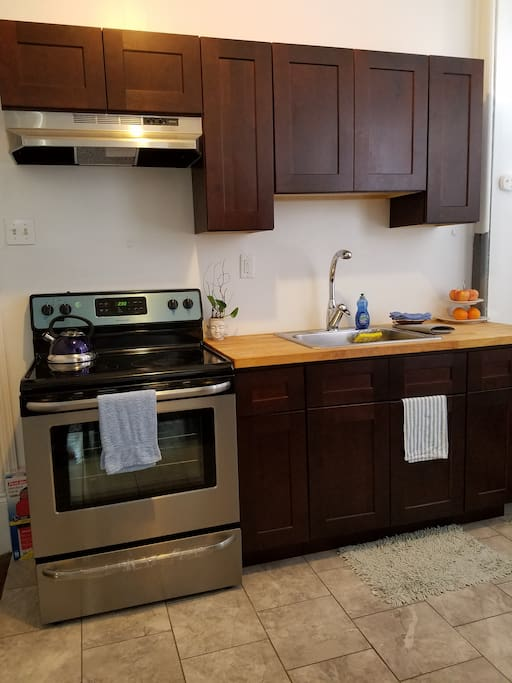 new renovated kitchen equipped with new range, refrigerator, pots, pans, cooking tools, and utensils