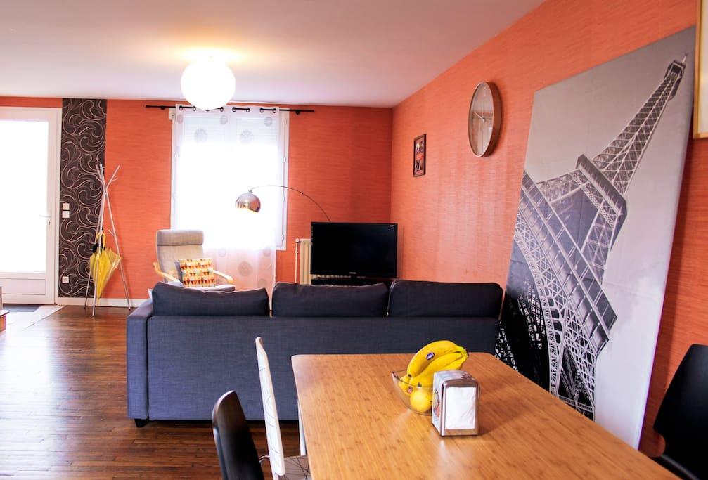 Salon avec canapé convertible, TV et table à manger