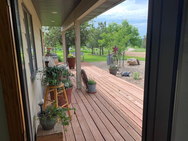 Front porch overlooking front yard and street with well-groomed yard.