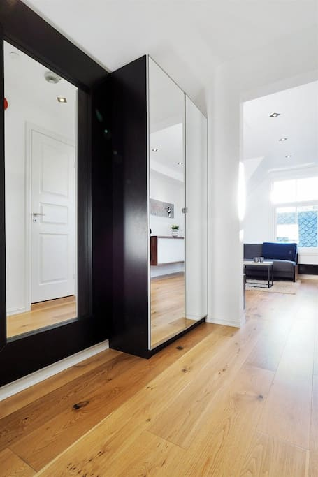 The entrance comes with two mirrored closets where you have more than enough space for your outerwear.